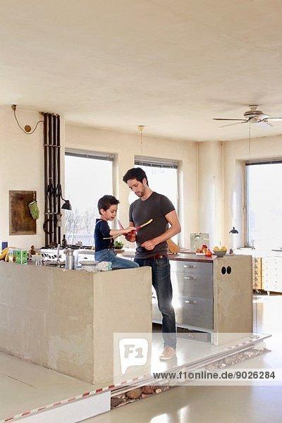 Vater und Sohn mit Spielzeugflugzeug in der Küche
