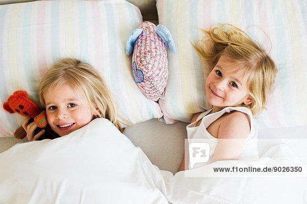Porträt von zwei jungen Schwestern  die nebeneinander im Bett liegen.