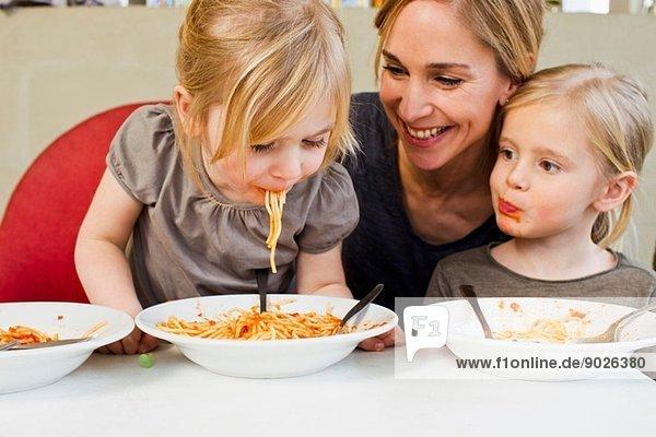 Mittlere erwachsene Mutter isst Spaghetti mit ihren beiden jungen Töchtern.