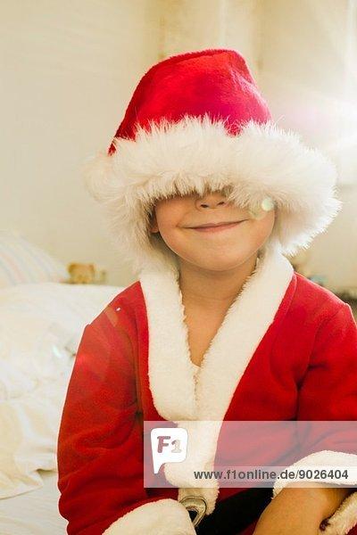 Porträt eines kleinen Jungen versteckt in der Weihnachtsmütze