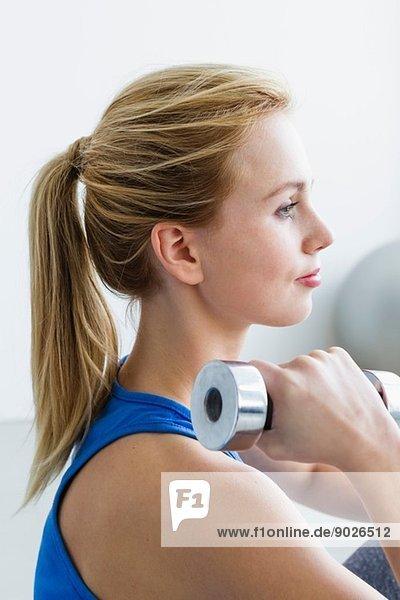 Junge Frau beim Heben von Gewichten