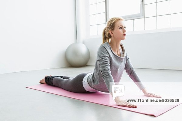 Junge Frau in Yoga-Pose auf Yogamatte