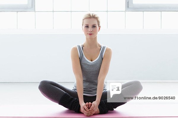 Junge Frau auf Yogamatte sitzend