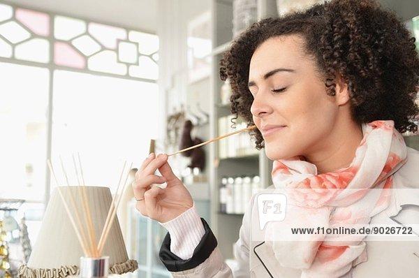 Junge Frau riecht Räucherstäbchen in der Boutique