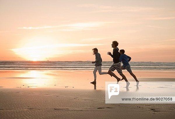 Mutter und Söhne  die am Strand laufen