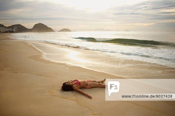 Reife Frau beim Sonnenbaden am Strand von Copacabana bei Sonnenuntergang  Rio De Janeiro  Brasilien