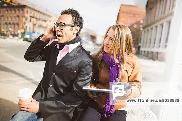 Junges Paar mit Handy und digitalem Tablett in New York  USA