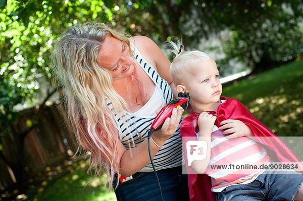 Mutter schneidet Kleinkind Söhne Haare mit Schere