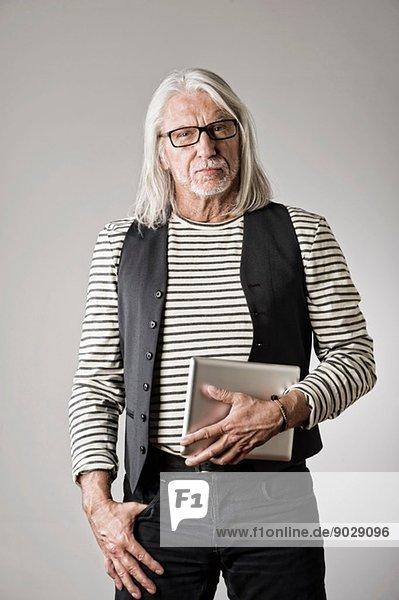 Porträt eines reifen Mannes  der ein digitales Tablett hält