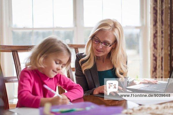 Mutter und kleine Tochter bei der Arbeit und Hausaufgaben im Esszimmer