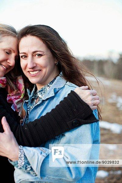 Porträt von reifen Frauen  die sich im Freien umarmen
