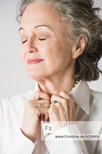 Porträt einer älteren Frau  Hände am Kragen  Augen geschlossen