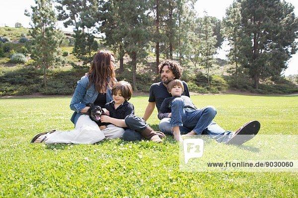 Familie mit zwei Jungen und Hund sitzend im Park