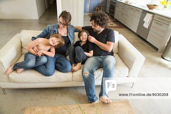 Familie mit zwei Jungen auf dem Sofa