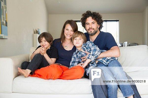 Porträt der Familie mit zwei Jungen auf dem Sofa