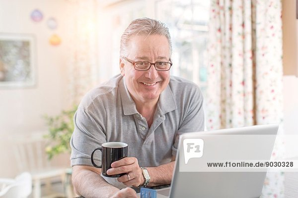 Erwachsener Mann zu Hause mit Laptop