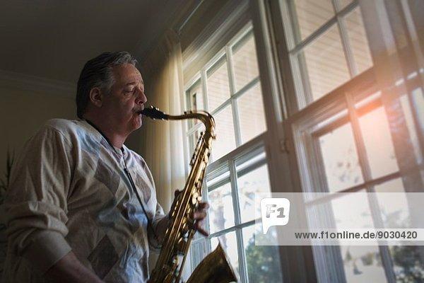 Erwachsener Mann zu Hause beim Saxophonspielen