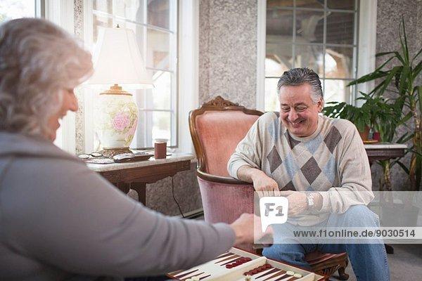 Reife Paare zu Hause beim Backgammonspielen