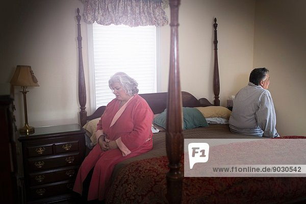 Mature couple sitting on opposite sides of bed