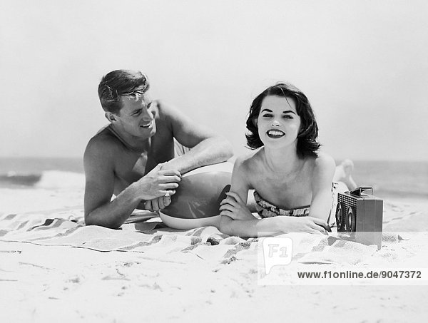 Couple lying on a beach towel listening to a radio