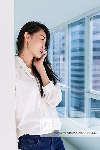 Young woman on corridor talking via ell phone  Thailand