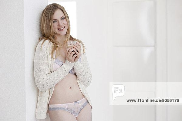 Lächelnde Frau in Unterwäsche lehnt an einer Wand