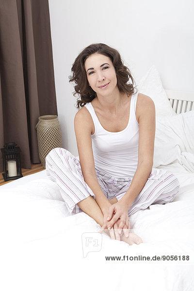 Lächelnde Frau sitzt im Bett