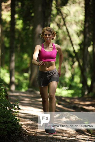 Woman jogging in forest  Spitzingsee  Bavaria  Germany