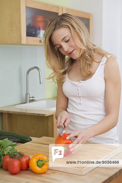 Junge Frau schneidet Gemüse in der Küche