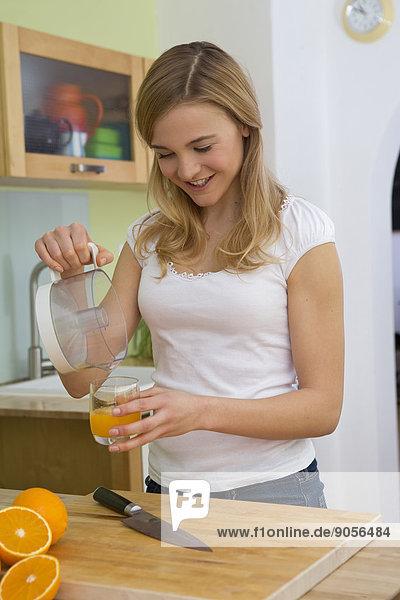 Junge Frau gießt Orangensaft in ein Glas