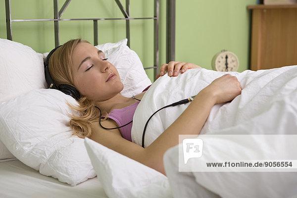 Junge Frau hört Musik im Bett