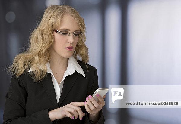 Blonde junge Geschäftsfrau mit Handy