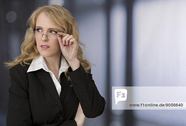 Blonde junge Geschäftsfrau denkt nach