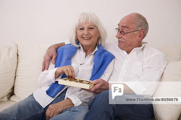 Seniorenpaar auf der Couch nascht Konfekt