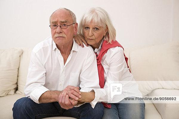 Ernstes Seniorenpaar sitzt auf der Couch