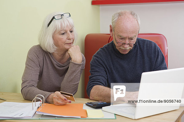 Seniorenpaar bezahlt Rechnungen am Laptop