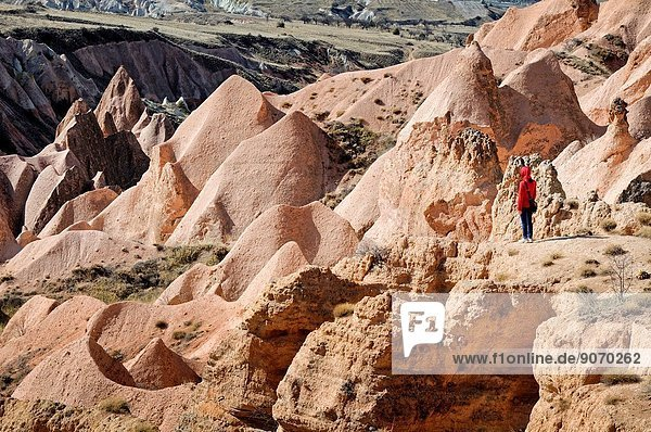 Trekker hiking in the Rose Valley among the fairy chimneys. Turkey  Central Anatolia  Nevsehir Province  Cappadocia  Goreme national park.