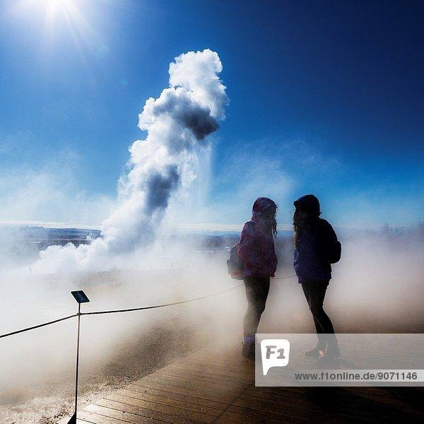 Teenager girls with Strokkur geyser in the background  Iceland.