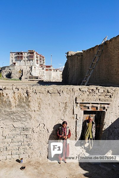 Ladakhi couple with the Stok Royal Palace in the background  residence of the Namgyal dynasty  Ladakh region  state of Jammu and Kashmir  India  Asia