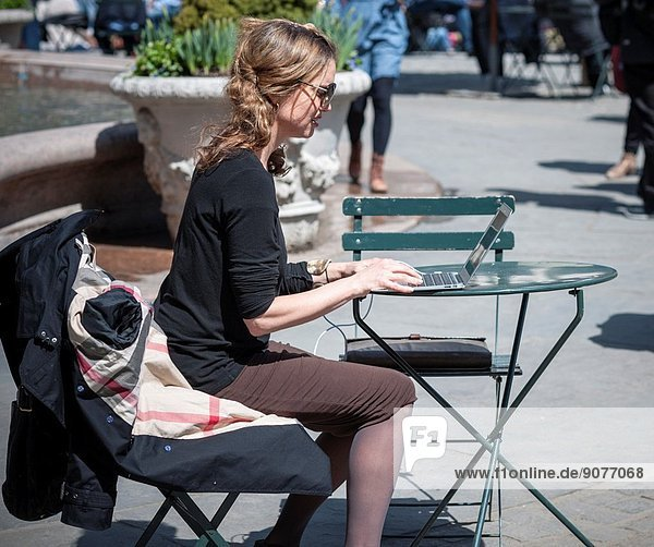 A woman uses her MacBook Air laptop in Bryant Park in New York City while enjoying the warm weather during her lunch hour