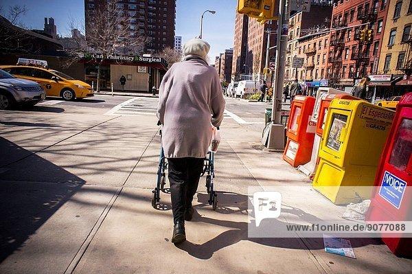 An elderly women with her walker in the New York neighborhood of Chelsea