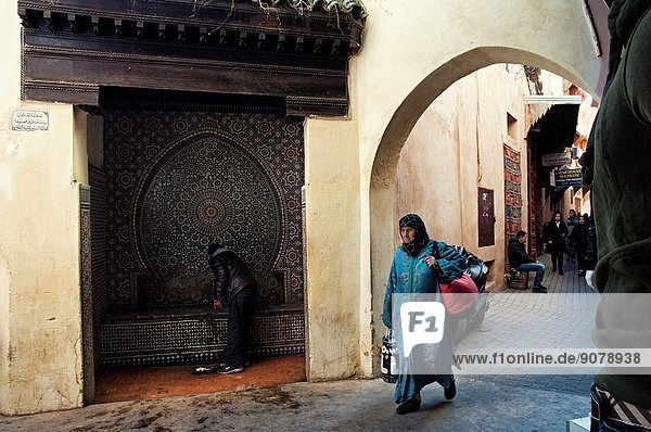 Man drinking water from a public fountain and elder woman in traditional clothing walking on the streets of the medina souk  Meknes  Morocco.