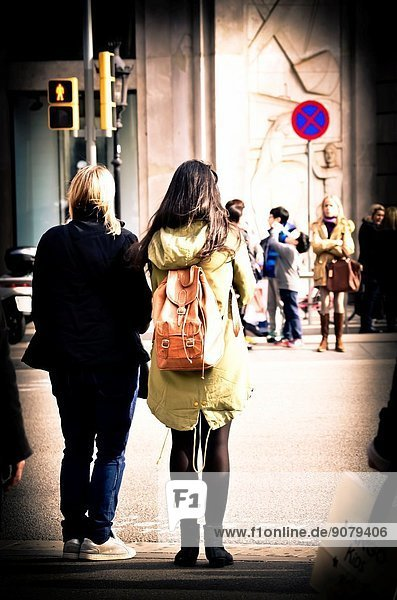 People waiting at a stoplight. Two women back  backpack. Barcelona  Catalonia  Spain.
