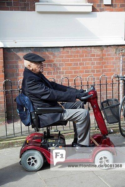 Man on mobility Scooter on Portobello Rd - London W11 - Uk.