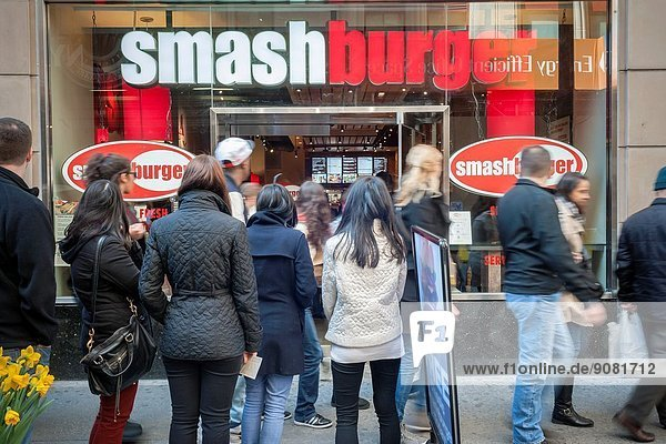 Burger lovers from far and wide descend on the new Smashburger restaurant in the shadow of the Empire State Building in New York on its grand opening day. The popular Colorado chain  which has a cultish following  opened its first Manhattan outpost bringing their burgers  smashed to order to the Big Apple. The fast casual restaurant has a loyal fan base and has 260 restaurants worldwide. The franchise welcomed their Manhattan customers by offering a free Classic Smashburger to each patron all day  with the line eventually stretching around the block.