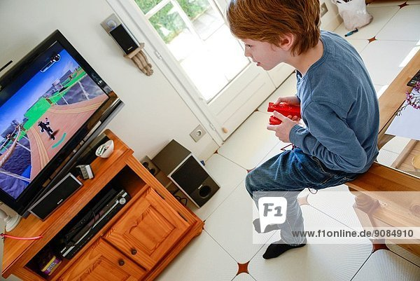 9 years old boy play Wii video game.