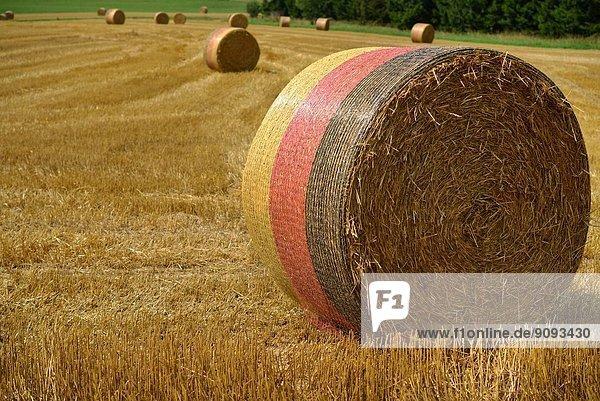 Strohballen,  überzogen mit einem Netz in den farben der deutschen Nationalflagge,  liegen auf einem Feld.