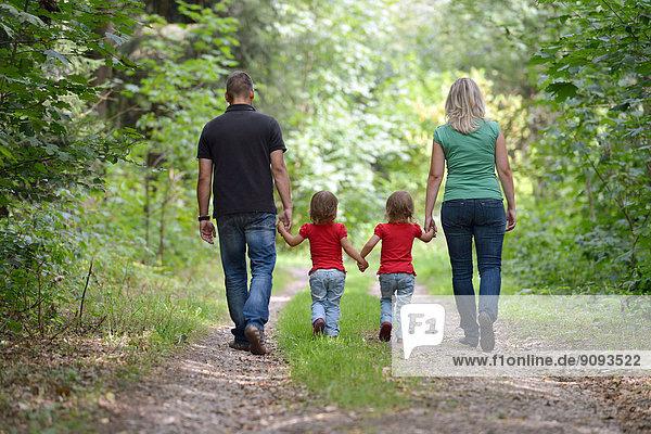 Eineiige Zwillingsmädchen mit ihren Eltern