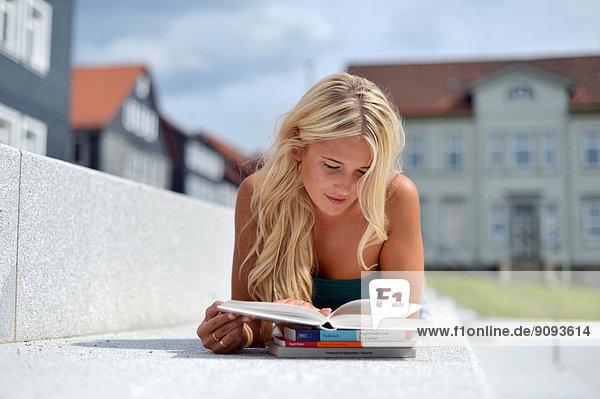 Eine junge blonde Frau liegt auf einer Steinbank und lernt.