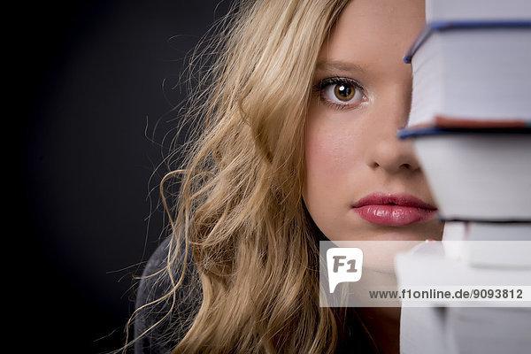 Porträt einer jungen Frau  die sich hinter einem Bücherstapel versteckt.